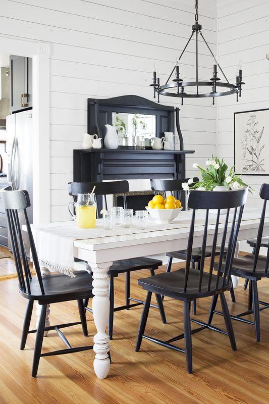 ظرفی از میوههای زرد رنگ در کنار ترکیب سیاه و سفید میز و صندلیها.